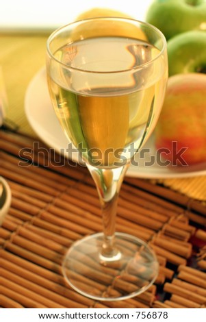 Soft focus shot of a glass of cider or fruit wine.