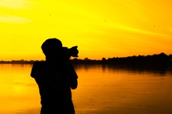 soft focus,Silhouette of the photographer in beautiful sunset.art tone,background