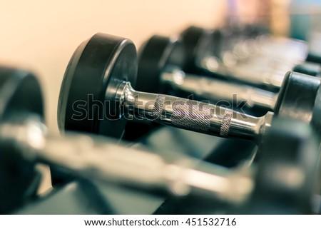 Soft focus the Sport equipment concept dumbbells on rack in gym. #451532716