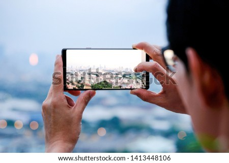 Soft focus .Young people take pictures of the buildings in the city. Sunrise time He uses a high-angle recording photo phone.Travel concepts and technology