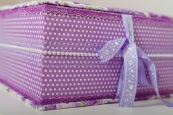 Soft focused shot of polka dot fabric covered box for weddig scrapbook album with purple lace, beads and ribbon.