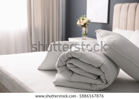 Soft folded blanket and pillows on bed indoors Foto stock ©