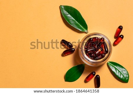 Soft gel omega 3 capsules with vitamin D in the glass jar on natural beige background top view. Immunity support supplements. Foto stock ©