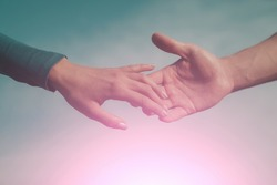 Soft, gentle touch of man and woman against sunny sky with flare in vintage mood. Love, connection, help concepts. Be hand in hand. two hands apart, reaching touching each other. Time concept.