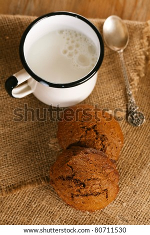 soft ginger cookies with milk in white enamel mug, shallow dof