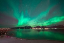 Soft green northern lights and many stars. In foreground a beach and in background mountains and lights from a village. Reflection of aurora in perfectly calm water. Lyngen Alps at Tromso in Norway.
