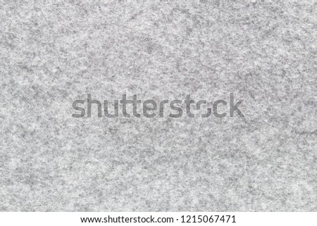 Soft grey felt material. Surface of felted fabric texture abstract background in gray color. High resolution photo.