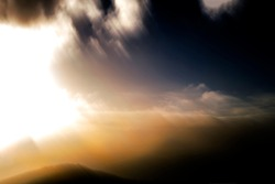 Soft, hazy, warm, expansive sky scape with bright sun behind clouds - abstract, motion-blurred background texture