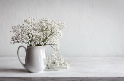Soft home decor, white jug, vase with white small flowers on a white vintage wall background and on a wooden shelf. Interior.