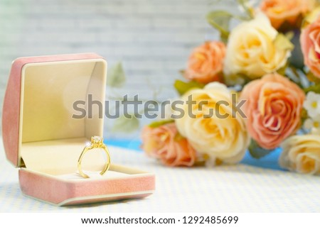 Photo of Soft image of golden diamond ring with light and beautiful bouquet rose. Special event. Valentine's day. Free space for any text design. Can be use for advertising, brochure, event.