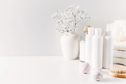 Soft light bathroom decor for advertising, design, cover, set of cosmetic bottles, bath accessories, white small flowers in vase, towel on white wooden shelf. mock up,copy space