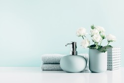 Soft light bathroom decor in mint color, towel, soap dispenser, white roses flowers, accessories on pastel mint background. Elegant decor bathroom interior.