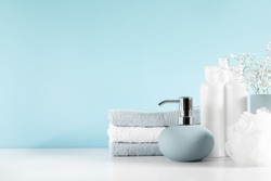 Soft light bathroom decor in pastel blue color, towel, soap dispenser, white flowers, accessories on white wood shelf. Elegant decor bathroom interior.