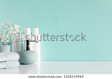 Soft light bathroom decor in pastel blue color, towel, soap dispenser, white flowers, accessories on white wood shelf. Elegant decor bathroom interior.