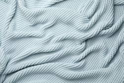 Soft light blue knitted plaid as background, top view