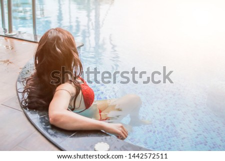 Soft Light & blurred photo, Asian women are relaxing by the pool to escape the hot summer of Thailand and are happy to relax during the holidays. Relaxation concept in summer
