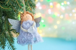 Soft light Christmas background, close-up of a soft angel with wings on a Christmas tree on a light bokeh background. Space for text. Greeting card, greeting card, happy new year and merry Christmas.