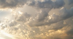 Soft light cloudy sky. Golden, yellow, orange, pearl, white clouds at sunset. Beautiful Cumulus clouds in the sky in the evening or in the morning.