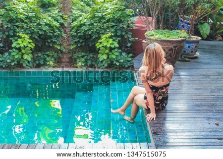 Soft Light & Smooth Focus, Asian women are relaxing by the pool to escape the hot summer of Thailand and are happy to relax during the holidays. Relaxation concept in summer #1347515075