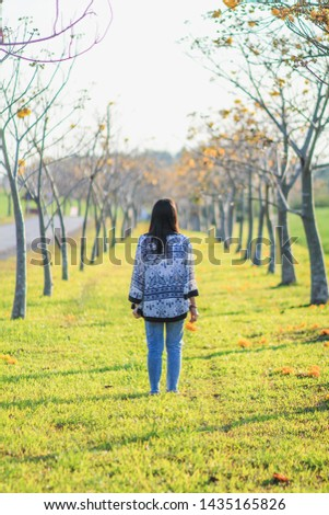 Soft light,The woman walked along the path in the park to aim for the goal that she had intended for herself and prayed for the blessings from the Lord in order for her to achieve the goal set.