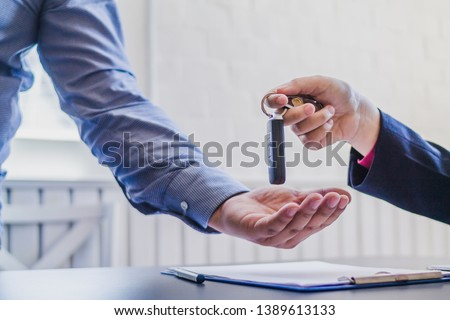 Soft Light,Young businessmen have delivered the keys to those who come to buy a car after agreeing to enter into a sales contract and a loan agreement for use in car payment installments. #1389613133