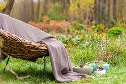 Soft luxury brown blanket on whicker chair in beautiful garden