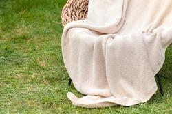 Soft luxury knit blanket on whicker chair on gren grass