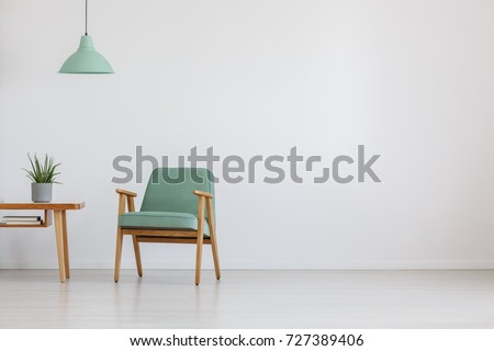 Soft mint green chair in retro style in open space with mint lamp and plant on wooden table #727389406
