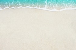 Soft ocean wave on white sandy beach background