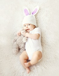 Soft photo of sweet cute baby in knitted hat with a rabbit ears and teddy bear lying on the bed, top view