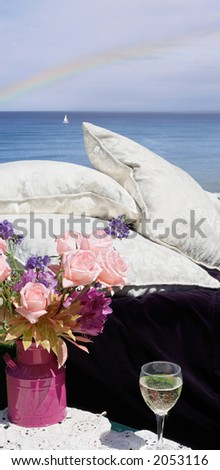 Soft pillows, wine, roses...relax and take in the view - stock photo