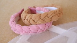 Soft pink and brown color braided headband made out of chiffon and tulle fabric texture. A hair band or headpiece with braid pattern.