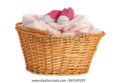 Soft pink baby blanket and booties in a wicker basket, isolated on white