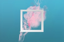 Soft pink color paint smoke explosion with square frame on classic blue to cyan gradient background. Creative minimal design composition with copy space.