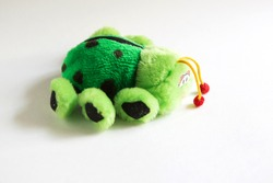 Soft plush toy for children - green ladybug. A beetle with sad eyes, red bells on its antennae, unrealistic color with black spots and large paws.Children's toy close-up, space for text