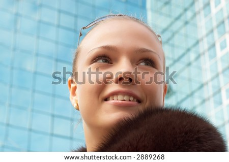 soft portrait of girl with fur, on the mirror building background