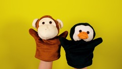 Soft puppet toys on hands on yellow background. Concept of puppet show. Close-up of hands with puppet monkey and penguin