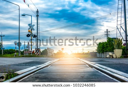 Soft railway on sky blue in sunset. Rail transport is a means of transferring of passengers and goods on wheeled vehicles running on rails or tracks. It pass road and traffic station for safety. #1032246085