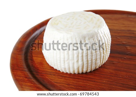 soft round cheese on board isolated on white