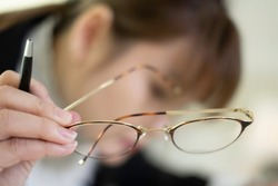 Soft, selective focus. Myopic woman reading book up close without glasses . Woman has short eyesight / myopia problem & need eyeglasses. Myopic woman need Lasik. Myopia & near sighted eyes concept.