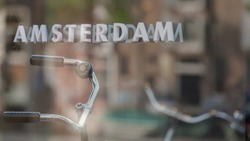 Soft selective focus of AMSTERDAM letters by outdoor bike shop window, Blurred reflection on the mirror with the bicycle handlebar from another side of street parked, Netherlands land of bicycles.