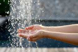 Soft selective focus of hands and droplets of water from shower with pool background