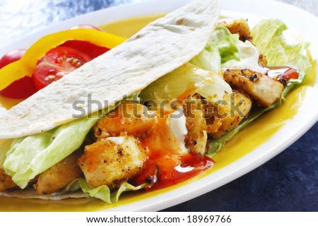 Soft tacos with spicy chicken, salad and sour cream.