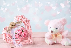Soft teddy bear and pink vintage wicker heart with bouquet of roses on pastel background with bokeh lights. Greeting card for Valentine's Day, International Women's Day and Birthday. Copy space.