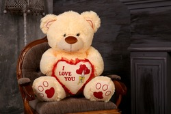 Soft toy bear sits on a chair. Large teddy fur bear in the interior. An unexpected surprise gift for a child or girl.