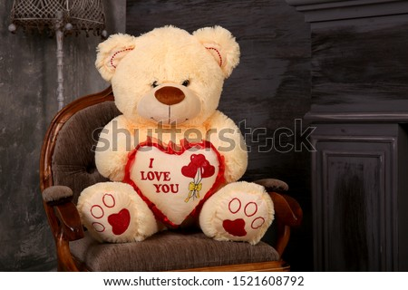 Soft toy bear sits on a chair. Large teddy fur bear in the interior. An unexpected surprise gift for a child or girl. Stock photo ©