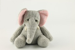 soft toy elephant sitting down, isolated on white background with copy space