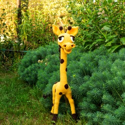 Soft toy giraffe with a long neck amigurumi among the greenery of the garden.