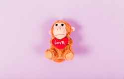 Soft toy monkey holding a heart in his hands on a purple background