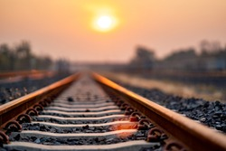 Soft track railway train on morning for transportation of travel in summer time, sunny of sun rise on morning on orange and yellow sky is beauty background